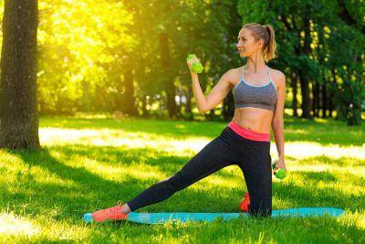 vrouw met groene dumbells in haar handen tijdens workout in het park